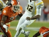 January 04 2011: Geno Smith #12 evaded Malliciah Goodman #97 and the rest of the Clemson defense during NCAA football Discover Orange Bowl between West Virginia and Clemson at Sun Life Stadium, Miami Florida.